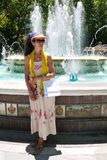 Frau, die durch Brunnen nach dem Einkauf sich entspannt Stockfoto