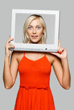 Frau, die durch das Bildschirmfeld schaut Stockbild
