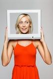 Frau, die durch das Bildschirmfeld schaut Stockfoto