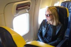 Frau, die durch das Fenster auf Flugzeug während des Fluges schaut Stockbilder