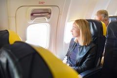 Frau, die durch das Fenster auf Flugzeug während des Fluges schaut Lizenzfreie Stockfotos