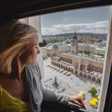 Frau, die durch das Fenster dem Marktplatz in Krakau betrachtet Lizenzfreie Stockfotos