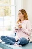 Frau, die durch das Fenster mit Kaffee sich entspannt Stockbild