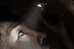 Frau, die durch das Loch mit lightabuse Konzept schaut Stockfotos