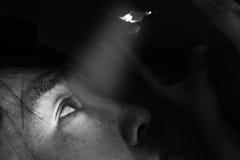 Frau, die durch das Loch mit lightabuse Konzept schaut Stockfotografie