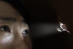 Frau, die durch das Loch mit lightabuse Konzept schaut Lizenzfreie Stockbilder