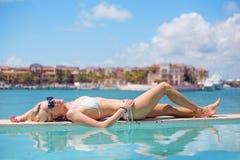 Frau, die durch das Pool ein Sonnenbad nimmt Stockbild