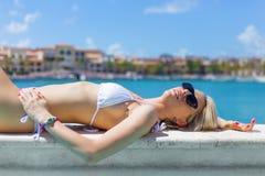 Frau, die durch das Pool ein Sonnenbad nimmt Stockbilder