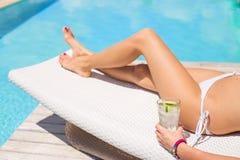 Frau, die durch das Pool mit Glas Auffrischung des kalten Getränks ein Sonnenbad nimmt Lizenzfreie Stockbilder