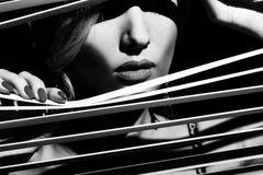 Frau, die durch den Jalousie späht lizenzfreies stockfoto