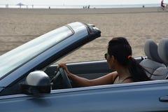Frau, die durch die Seite des Ozeanstrandes fährt Stockbilder