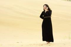 Frau, die durch die Wüste ersucht um Mobiltelefon geht Lizenzfreie Stockfotos