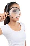 Frau, die durch ein Vergrößerungsglas schaut Lizenzfreie Stockfotos