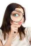 Frau, die durch ein Vergrößerungsglas schaut Stockbild