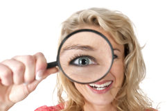 Frau, die durch eine Lupe mit großem Auge schaut Stockbild