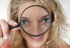 Frau, die durch eine Lupe mit großen Augen schaut Lizenzfreie Stockfotografie