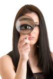 Frau, die durch eine Lupe schaut Stockfotografie
