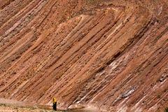 Frau, die durch eine Steinwüste in Marokko geht stockfotografie