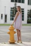Frau, die durch einen Feuerhydranten aufwirft Stockfotografie