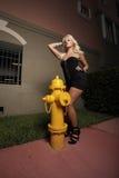Frau, die durch einen Feuerhydranten aufwirft Lizenzfreie Stockfotos