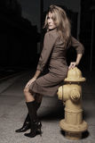 Frau, die durch einen frie Hydranten aufwirft Stockfotos