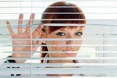 Frau, die durch einen Jalousie schaut lizenzfreie stockfotografie