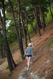 Frau, die durch einen Wald wandert Lizenzfreie Stockfotos