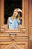 Frau, die durch Fenster einer Holztür schaut Lizenzfreies Stockbild