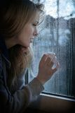 Frau, die durch Fenster mit Regentropfen schaut Lizenzfreie Stockfotografie
