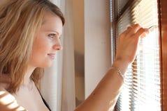 Frau, die durch Fenster schaut Lizenzfreie Stockbilder