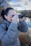 Frau, die durch Ferngläser schaut Lizenzfreie Stockbilder