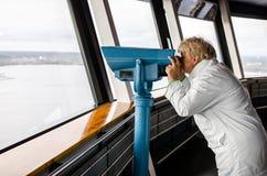Frau, die durch Ferngläser von Nasinneula-Turm schaut Lizenzfreie Stockbilder