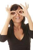 Frau, die durch Finger schaut Stockfoto
