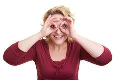 Frau, die durch Finger schaut Lizenzfreie Stockbilder