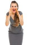 Frau, die durch geformte Hände des Megaphons schreit Stockfotos
