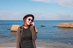 Frau, die durch Handy nennt und auf Strand geht Stockfotografie