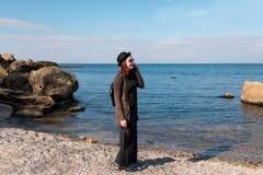 Frau, die durch Handy nennt und auf Strand geht Lizenzfreies Stockfoto