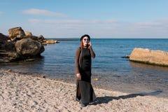 Frau, die durch Handy nennt und auf Strand geht Stockfotos
