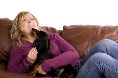 Frau, die durch Hund geleckt erhält Stockbilder