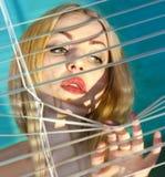 Frau, die durch Jalousie L schaut Stockfoto