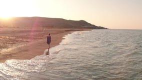 Frau, die durch die Küstenlinie geht stock video footage