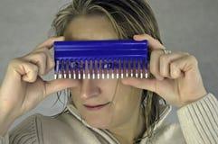 Frau, die durch Kamm schaut Lizenzfreie Stockfotografie