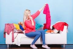 Frau, die durch Kleidung auf unordentlicher Couch schaut lizenzfreie stockfotos