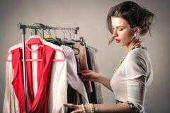 Frau, die durch Kleidung sortiert stockfotos