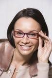 Frau, die durch neue Gläser schaut Lizenzfreies Stockfoto