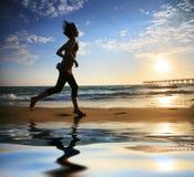 Frau, die durch Ozean läuft Stockbilder