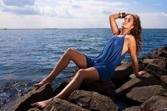 Frau, die durch Ozean sich entspannt lizenzfreie stockfotos