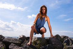 Frau, die durch Ozean sitzt Stockbilder