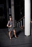 Frau, die durch Pfosten aufwirft Stockfotografie