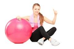 Frau, die durch pilates Ball sitzt und Daumen aufgibt Lizenzfreie Stockfotos
